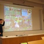 Herr Cornelius Müller rundete den Workshoptag als zweiter Gastredner ab - Im Hintergrund ein Sreenshot des Spiels World of Warcraft.